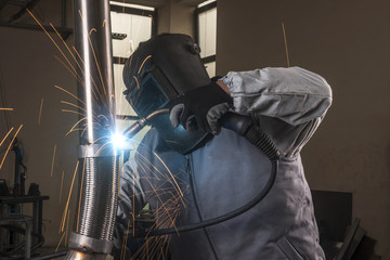 industrial arc welder working in factory