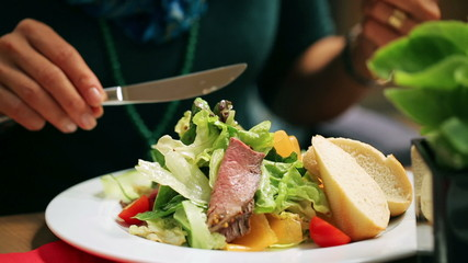 Woman eating salad at the restaurant, closeup, steadycam shot
