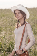 girl in a white cowboy hat smiling at the grassy field