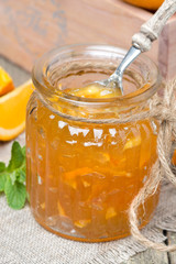 delicious orange marmalade in a glass jar, vertical