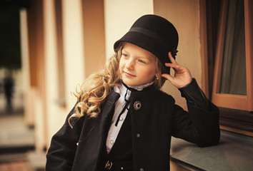 Little girl in a black hat and coat looking away