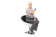 Woman holding a cell phone seated in modern chair