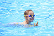 Joyful child in swimming glasses in the outdoor pool.