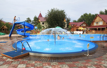Children's pool with a fountain and a slide.