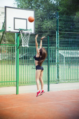 Beautiful young woman playing basketball outdoors