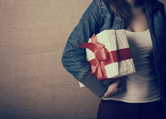 Portrait of attractive cheerful girl holding gift box with red b