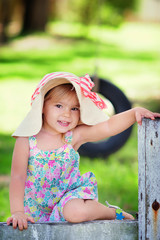 Portrait of a happy little girl in countryside at summer day