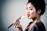 Young beautiful asian woman eating sushi, toned image