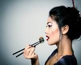 Young beautiful asian woman eating sushi with chopsticks, toned