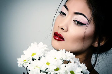 Young beautiful asian woman's portrait with white flowers, studi
