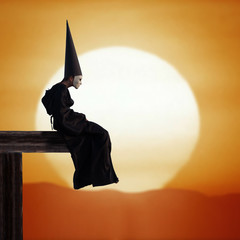 Strange person in black cloak and dunce hat at sunset