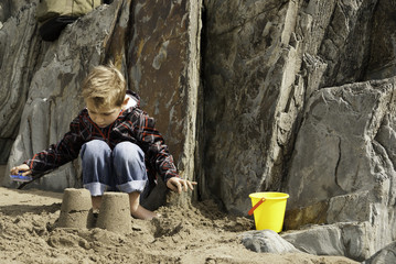 Boy building Sandcastle on Rocky Beach