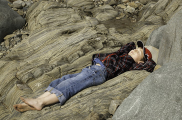 Boy Lying on Rock on the Beach