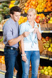 Young couple with shopping list decides what to buy