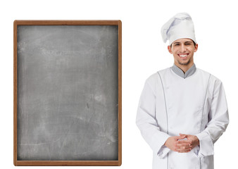Portrait of smiling chef cook standing near grey menu blackboard