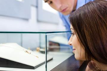 Girl with man selects expensive jewelry at jeweler's shop