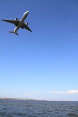 着陸する飛行機(B777)と海