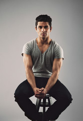 Muscular young male model sitting on stool