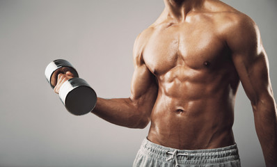 Fit young man exercising with dumbbells