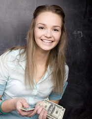 portrait of happy cute student with money, near blackboard