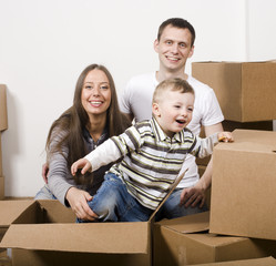 stock-photo-smiling -family-in-new-hous e-playing-with-boxe s