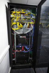 Modern black server cabinet with network equipment and wires