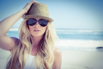 Stylish blonde looking at camera on the beach