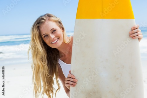 Blonde surfer holding her board smiling at camera