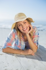 Pretty blonde smiling at camera at the beach lying on the sand