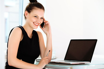 Businesswoman talking on mobile phone in a office