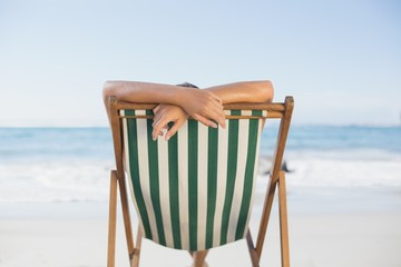 Woman relaxing in deck chair on the beach