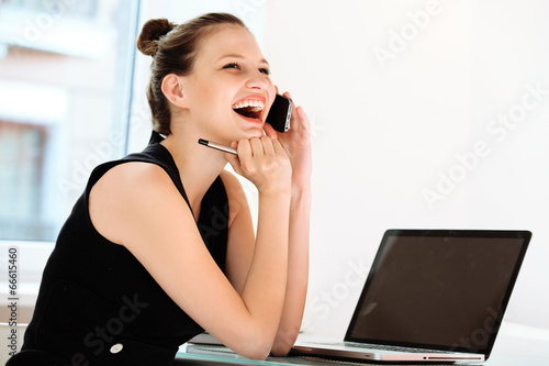 Businesswoman talking on mobile phone in a office - 66615460