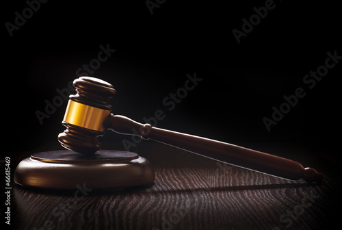 Poster Wooden gavel on a textured dark wood surface