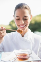 Smiling beauty therapist holding plate with honey