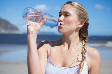 Focused fit blonde drinking water on the beach