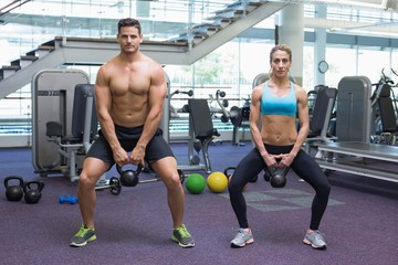Bodybuilding man and woman lifting kettlebells in a squat