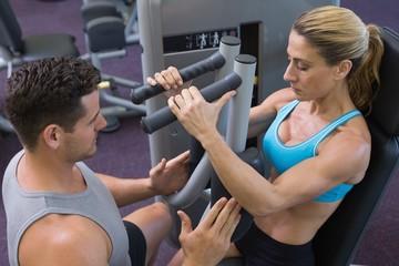 Personal trainer coaching female bodybuilder using weight machin