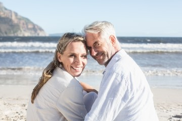 Couple sitting on the beach under blanket smiling at camera