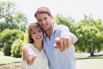 Cute couple pointing to the camera in the park
