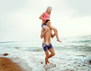 young couple walking along the seashore, girl sits on the guy's