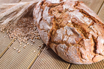 Fresh bread with wheat on the wooden background