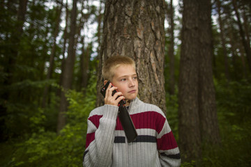 Boy in forest talking on the phone