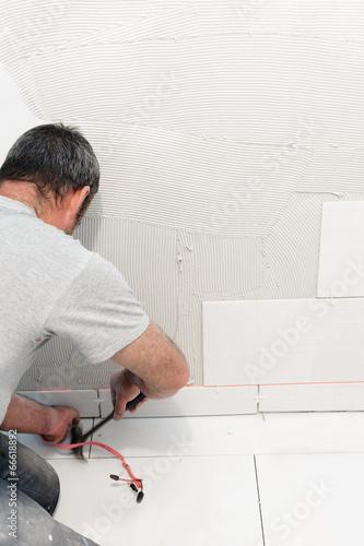 Worker installing ceramic tiles