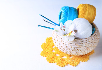 Colorful clews and crochet hooks in wicker basket