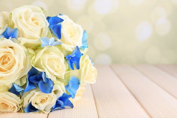 Beautiful wedding bouquet with roses on wooden table