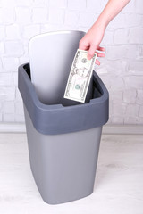 Throwing away your money on grey wall background