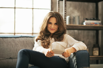 Happy young woman writing sms in loft apartment