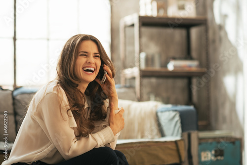 Portrait of smiling young woman talking cell phone  - 66622240