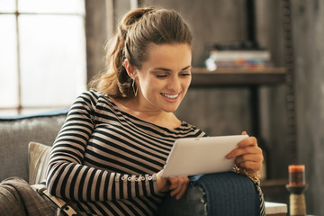 Happy young woman sitting on sofa and using tablet pc