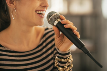 Closeup on happy young woman singing with microphone